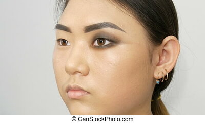 Professional stylist make-up artist makes up the smoky eye...