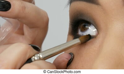 Professional stylist make-up artist makes up the smoky eye of an Asian girl model face in visage studio close up view