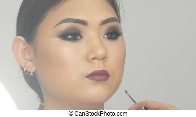 Professional stylist make-up artist with special brush paints dark red lips with a special brush of Asian girl model face in visage studio close up view
