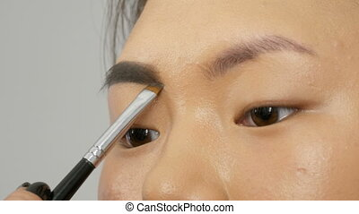 Professional stylist make-up artist with special brush paints eyebrows with eyebrow shadows of an Asian girl model face in visage studio close up view