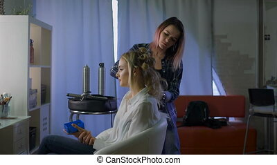 Professional Stylist makes hairstyle for your constant client. Business woman in a beauty salon.