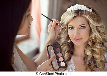 Professional Stylist makes makeup bride on the wedding day....
