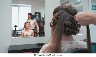 Professional stylist makes the curls to an attractive brown-haired using a hot curling
