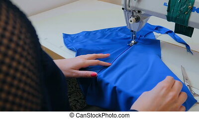 Professional tailor, fashion designer sewing clothes with...