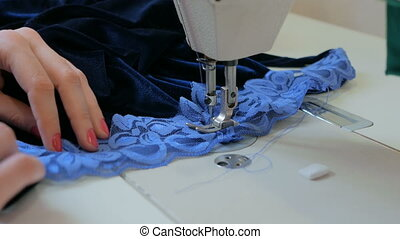 Professional tailor, fashion designer sewing clothes with sewing machine