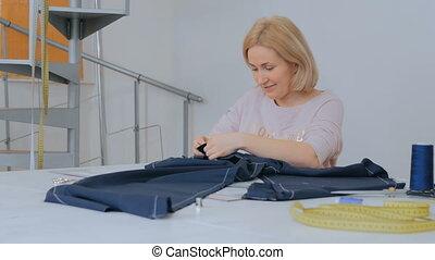 Professional tailor, fashion designer working at sewing studio