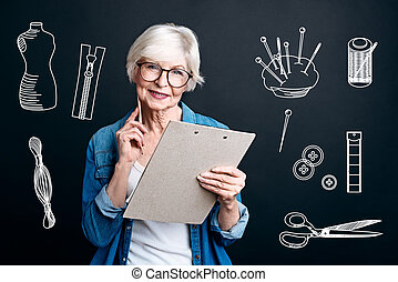 Professional tailor holding a clipboard while being in her atelier