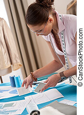 Professional tailor working with fashion sketches at studio
