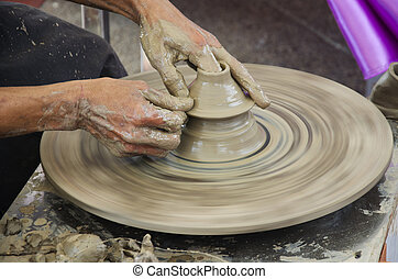 Professional thai old man using mechanic pottery made earthenware for show in traditional culture thai festival at Koh Kret Island