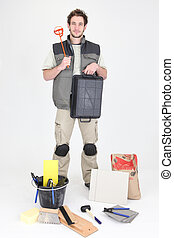 Professional tile fitter holding a mixer and a tray