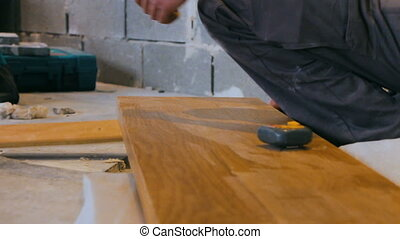 Professional tiling carpenter measures and marking a wooden...
