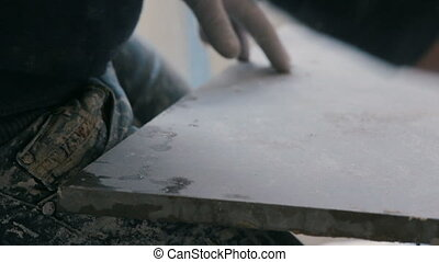 Professional tiling worker measures and marking a tile with...
