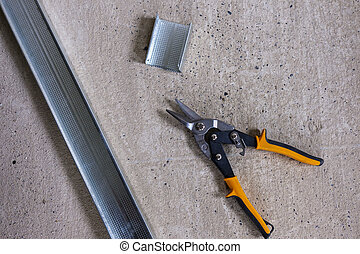 Professional tin snips or metal shears with yellow handles, viewed from above with pieces of metallic profile for wall construction