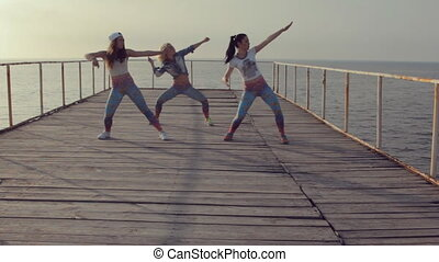 Professional twerk by talented young teenagers on a wooden pier near the sea