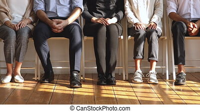 Professional unemployed business people sit on chairs, legs ...