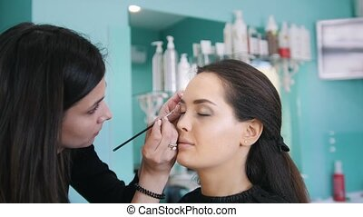 Professional visage artist doing make-up with black eyeliner...