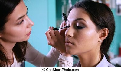 Professional visage artist doing make-up with black eyeliner...