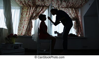 Professional visagiste does make-up for fiancee in dark room.