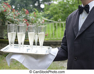 Professional waiter in uniform is serving champagne