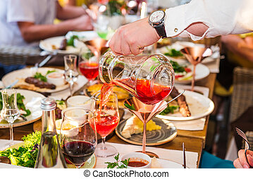 Professional waiter in uniform serving drinks to guests of event. Catering or celebration concept. Service at business, corporate meeting, party, weddings. Selective focus, space for text