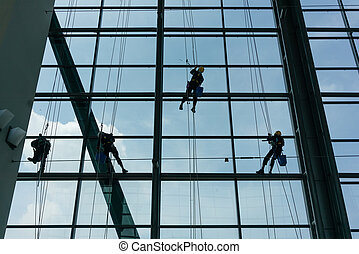 Professional window cleaners climbing up facade on ropes