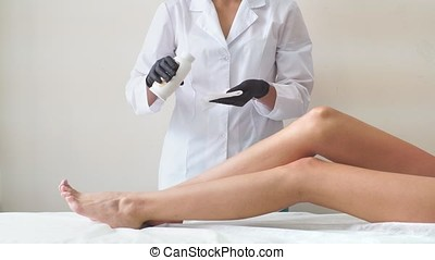 Professional woman at spa beauty salon doing epilation by...