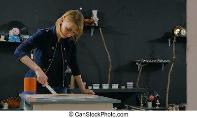 Professional woman decorator, designer painting wooden...