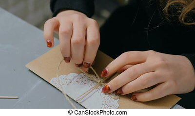 Professional woman decorator working with kraft paper and wrapping envelope