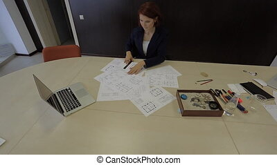 professional woman lays the blueprint schemes at home and begins to work with them