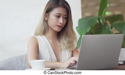 Professional woman working on laptop computer and drinking coffee