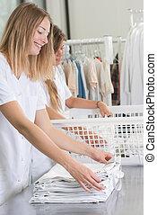 Professional women folding laundry