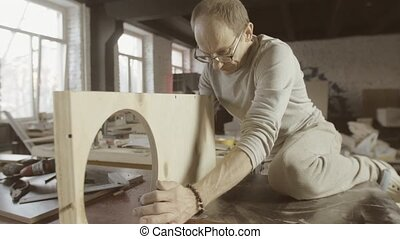 Professional woodworker connects two wooden polished board by hammer. Assembly