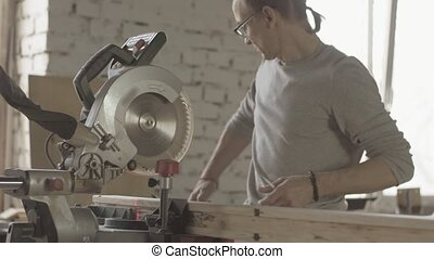 Professional woodworker cut long wooden board by circular saw. Furniture.
