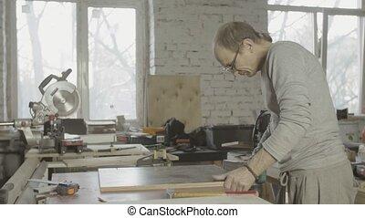 Professional woodworker polish edge of wooden board by belt sander machine