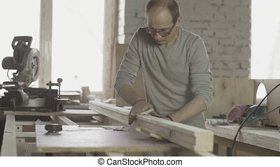 Professional woodworker polish long wooden board by special sponge. Furniture.