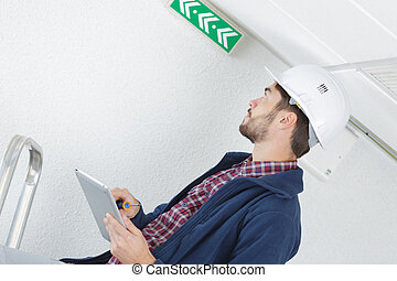professional worker checking exit sign