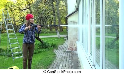 professional worker cleaning dirty windows with high pressure water jet