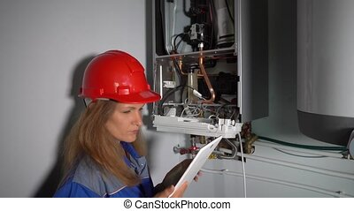 Professional worker inspecting new gas heating system at ...