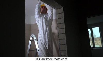 Professional worker making drywall ceiling holes for lighting installation