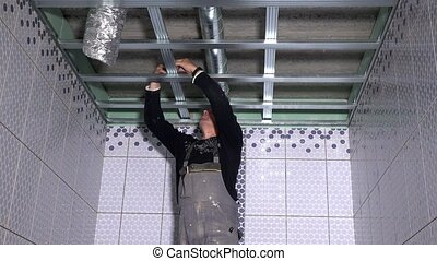 Professional worker man fix ceiling profiles. Static closeup...