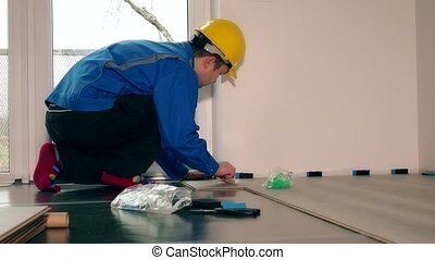 Professional worker man laying wooden laminate floor in new...
