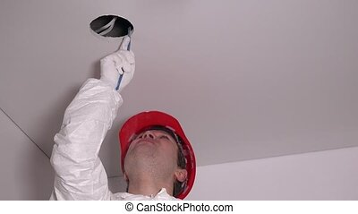 Professional worker man make drywall ceiling holes for lighting installation