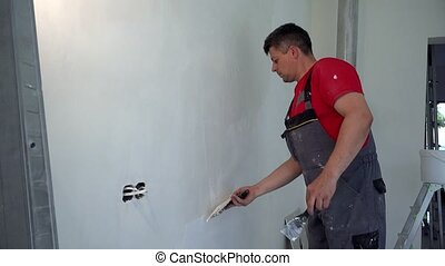 Professional worker man plastering wall with trowel. Static ...