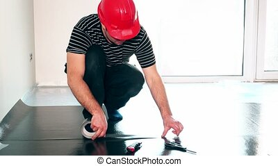 Professional worker man taping down flooring underlay with...