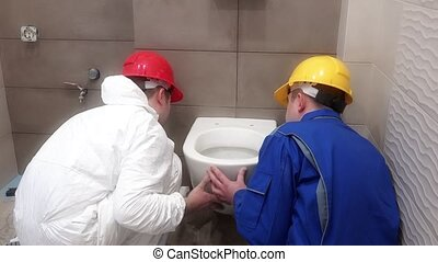Professional worker men hanging heavy toilet bowl pan in new...