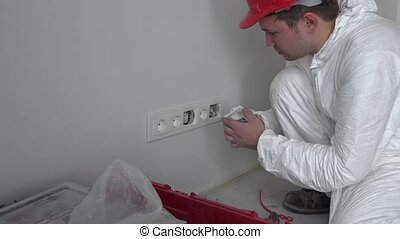 Professional worker mounting wall socket outlet on new flat house building