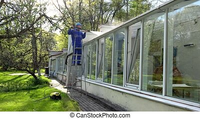 Professional worker on ladder washing glasshouse roof with...