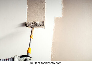 professional worker plastering a wall, painting with paint brush decoration on interior walls
