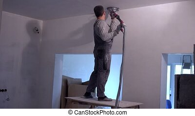 Professional worker polishing ceiling with grinding...