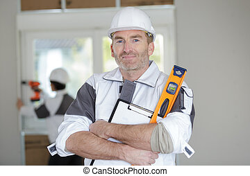 professional worker posing with spirit level at construction site